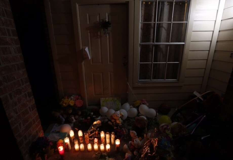 Flowers, balloons, and candles have been placed on the door step of the house where eight people were killed Sunday, Aug. 9, 2015, in Houston. Photo: Cody Duty