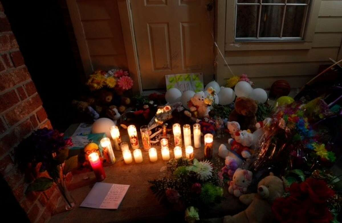 Flowers, balloons, and candles have been placed on the door step of the house where eight people were killed Sunday, Aug. 9, 2015, in Houston.