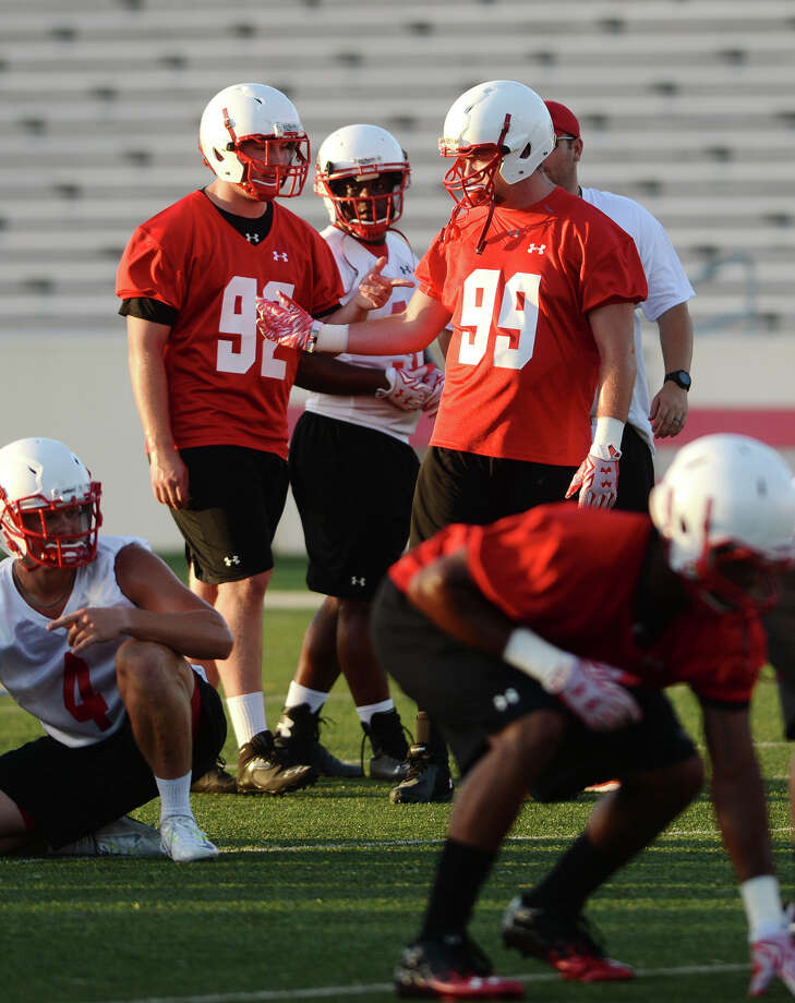 Cardinal players Koby Couron, No. 92, and Corbin Carr, No. 99, talk while they wait for their turn during drills Friday. The Lamar Cardinals held their opening practice Friday evening at Provost Umphrey Stadium. Photo taken Friday 8/7/15 Jake Daniels/The Enterprise Photo: Jake Daniels / ©2015 The Beaumont Enterprise/Jake Daniels