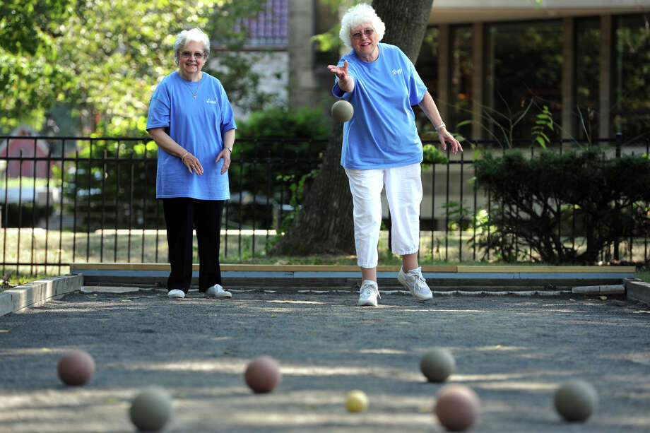 "Reggie Vrabel, right, pitches a ball during a game of bocce at the Baldwin Center, in Stratford, Conn. Aug. 27, 2014. She is seen here with Janet Onze. They are both members of the ""Bocce Rollers"", a group of senior women who play on the center's bocce court every Wednesday morning. Photo: Ned Gerard / Ned Gerard / Connecticut Post"