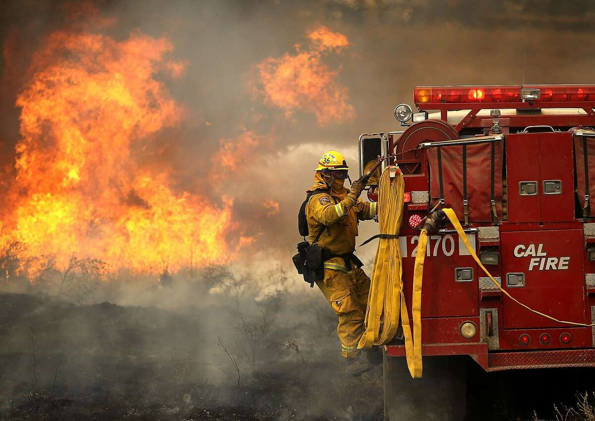 LOWER LAKE, CA - JULY 30: A Cal Fire firefighter rides on the side of a fire engine while battling the Rocky Fire on July 30, 2015 in Lower Lake, California. Over 600 firefighters are battling the Rocky Fire that erupted to over 8,000 acres since it started on Wednesday afternoon. The fire is currently zero percent contained and has destroyed three homes. (Photo by Justin Sullivan/Getty Images)
