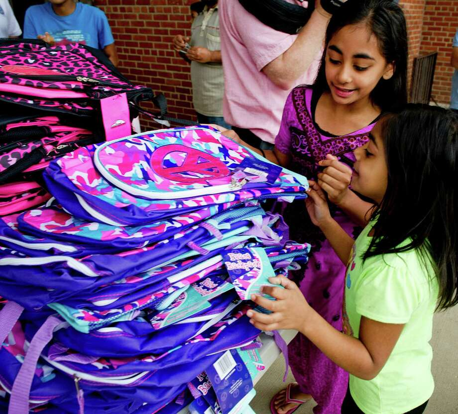 Salima Shafi, 11, left, helps her sister, Rahima, 7, as they choose backpacks during last year's annual giveaway at the Stamford Police Department. Photo: Lindsay Perry / Hearst Connecticut Media / Stamford Advocate
