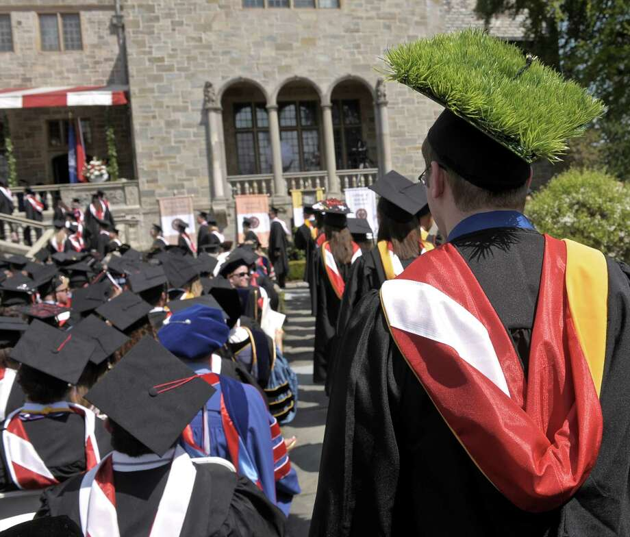 Jesse Conklin, from Agawam, Mass, lets the grass on his mortarboard receive a little extra light as he waits to receive his degree during the 2015 Fairfield University  Commencement held on the Bellarmine Terrace of Fairfield University, Sunday morning, May 17, 2015, in Fairfield, Conn. Conklin received his degree from the College of Arts and Sciences. Photo: H John Voorhees III / Hearst Connecticut Media / The News-Times