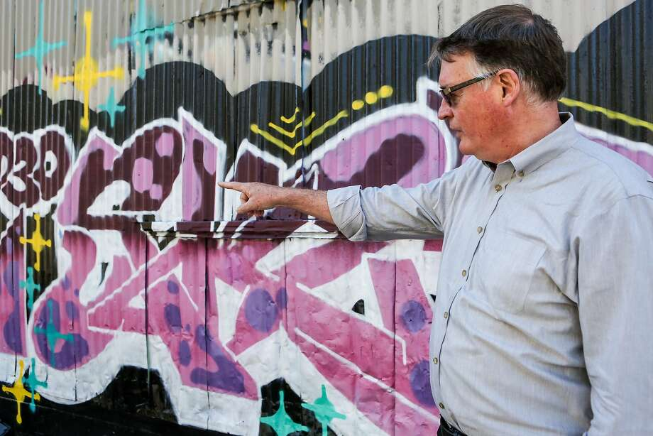 Ian Birchall checks out a mural near his business around South Van Ness Avenue. Photo: Amy Osborne, Special To Chronicle