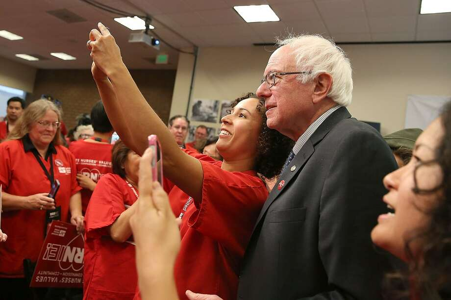 Independent presidential candidate U.S. Sen. Bernie Sanders (I-VT) takes a selfie with nurses at a campaign rally on August 10 in Oakland. However, selfies at voting booths are becoming controversial since New Hampshire banned voting-booth photos and created a fine of up to $1,000 for putting a photo that contains a completed ballot on social media. Photo: Justin Sullivan, Getty Images