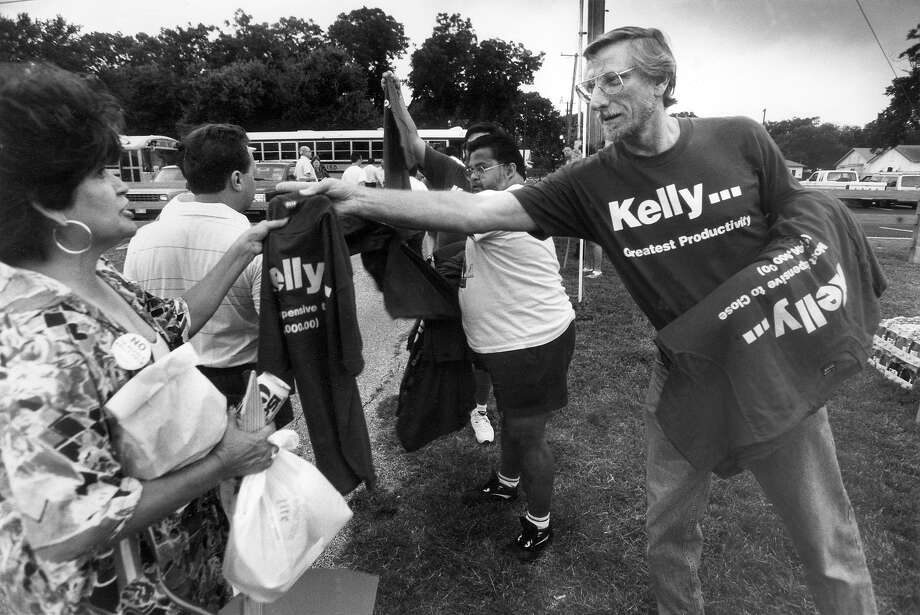 Kelly employee James Steele hands out T-shirts as workers from the base board buses en route to a 1993 base-closure hearing in Corpus Christi. Rumors surfaced the following year that Kelly's air logistics center would be closed by the government. File Photo Photo: Express-News File Photo / SAN ANTONIO EXPRESS-NEWS