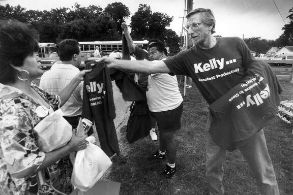 Kelly employee James Steele hands out T-shirts as workers from the base board buses en route to a 1993 base-closure hearing in Corpus Christi. Rumors surfaced the following year that Kelly's air logistics center would be closed by the government. File Photo