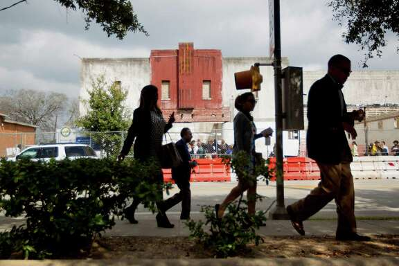 """A group of people leave the breaking ground ceremony for the restoration of the De Luxe Theater at 3303 Lyons Ave. in the Fifth Ward Monday, Feb. 17, 2014, in Houston.  The once popular theater and exhibit space, closed since 1973, will undergo major renovations and open in late 2014. The restored facility will offer a 125 seat proscenium theatre, including laboratory & class room space, a box office, lobby, and administrative offices with programming offered by Texas Southern University.  Support came from The City of Houston Housing and Community Development Department, Texas Southern University and the Fifth Ward Community Redevelopment Corporation and the """"Lyons Avenue Renaissance,"""" hosting this event."""