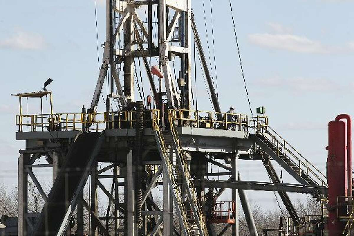Work continues on a drilling rig off Texas State Highway 72 east of Tilden, Texas, Thursday, February, 19, 2015. A drop in the price of crude oil has led to a slow down activity in the Eagle Ford Shale play. (Jerry Lara/ San Antonio Express-News)