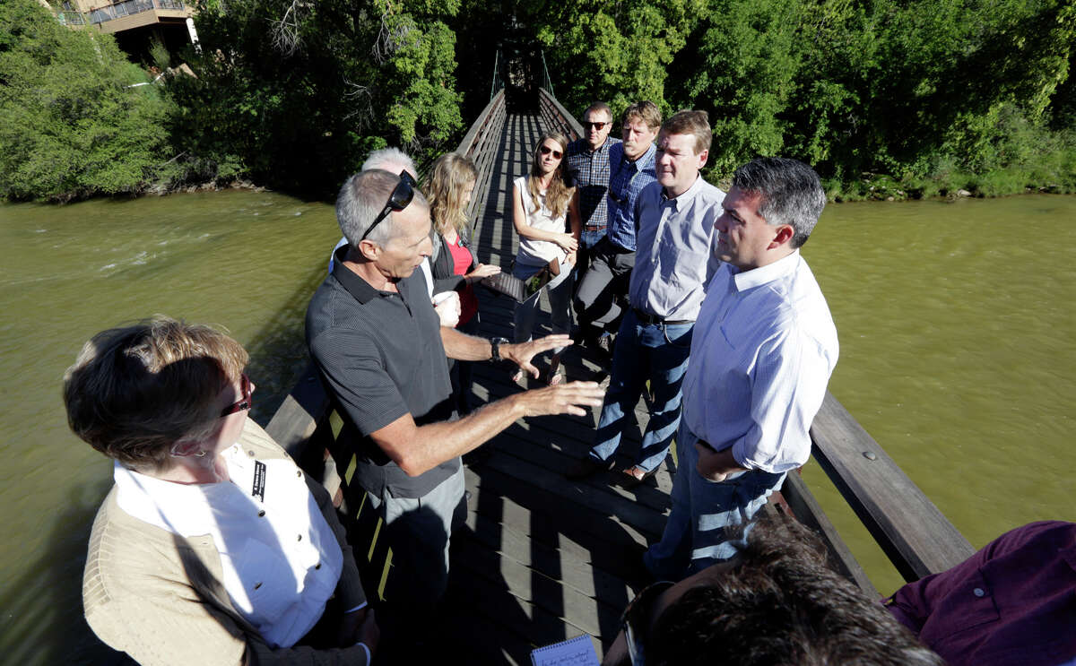 Andy Corra, left, co-owner of 4 Corners Riversports in Durango, Colo., talks with Colorado U.S. Sens., Cory Gardner, front right, and Michael Bennet, middle right, on a bridge over the Animas River in 2015. (Jerry McBride/The Durango Herald via AP) MANDATORY CREDIT