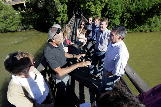 Andy Corra, left, co-owner of 4 Corners Riversports in Durango, Colo., talks with Colorado U.S. Sens., Cory Gardner, front right, and Michael Bennet, middle right, on a bridge over the Animas River, Sunday, Aug. 9, 2015. in Durango. An Environmental Protection Agency official said Sunday she doesn't believe wildlife will suffer significant health impacts from the large volume of wastewater that spilled from a nearby abandoned mine. (Jerry McBride/The Durango Herald via AP) MANDATORY CREDIT