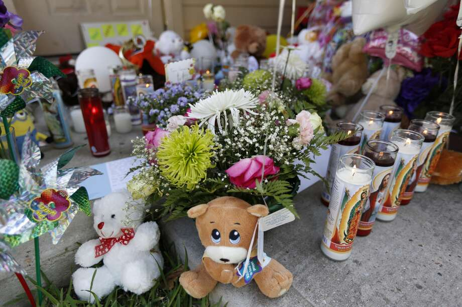 A memorial has been placed on the door step of the house where eight people were killed Sunday, Aug. 9, 2015, in Houston.