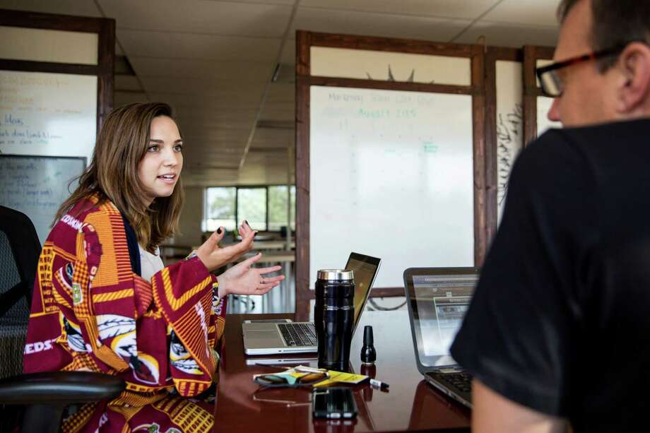 Phoebe McPherson wears a Snuggie blanket while talking to colleague Rick Rickert at the LifeFuels office in Reston, Va., Most office buildings set temperature based on a formula based on the metabolic rates of men. This formula is now being challenged to reduce energy consumption. Photo: Drew Angerer / New York Times / NYTNS