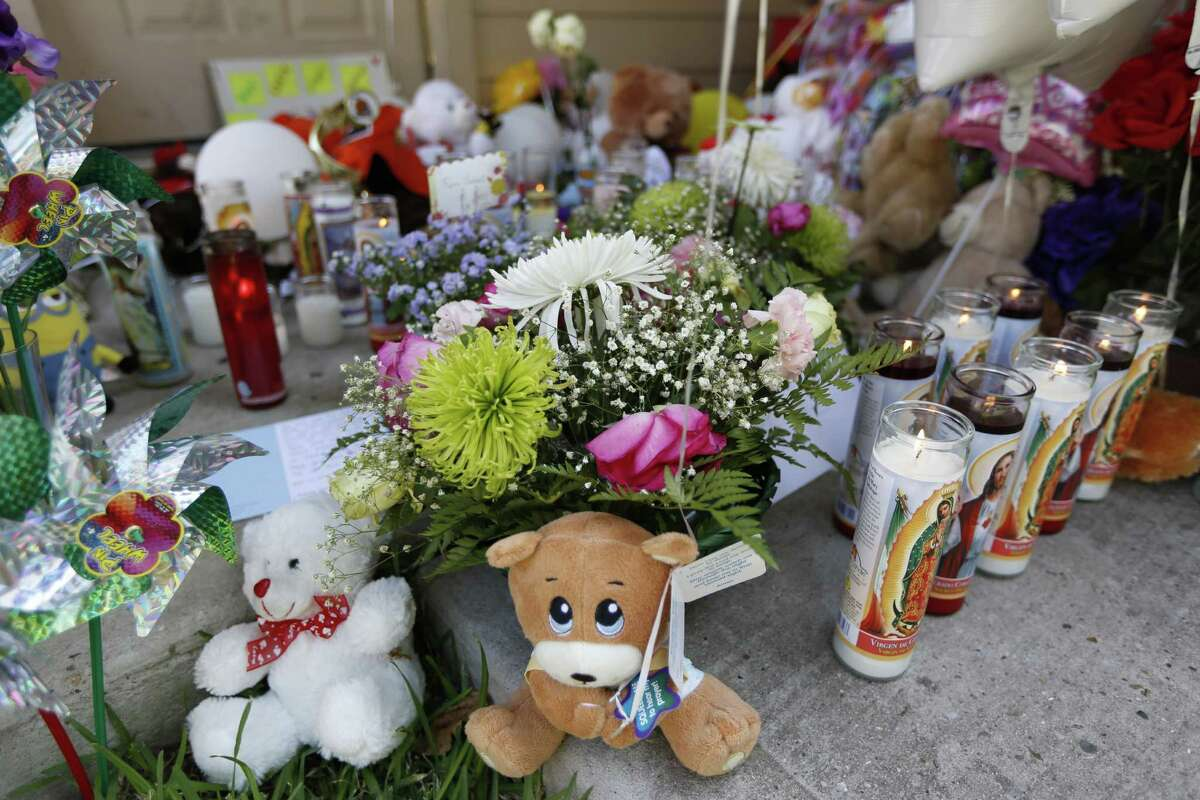 A make shift memorial grows Monday, Aug. 10, 2015, in Houston outside of the home Valerie Jackson, 2211 Falling Oak, where 6 children and two adults were murdered.