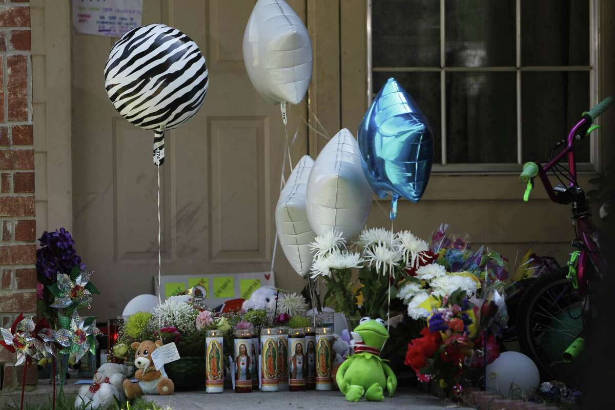 The scene outside of the home Valerie Jackson, 2211 Falling Oak, where 6 children and two adults were Monday, Aug. 10, 2015, in Houston.