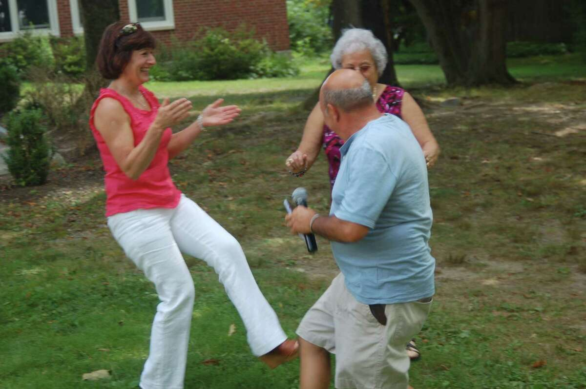 Anna Marpowicz, left, joins Filomena Castrovillari and Giuseppe Leale as they marked the Feast of St. Lawrence with music and dancing at St. Michael Church on Sunday.