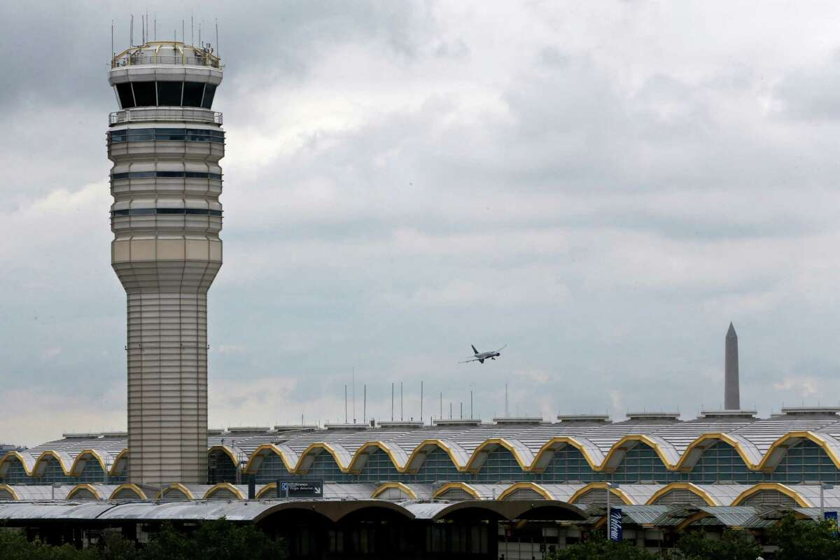 An airplane flies past the air traffic control tower at Washington's Ronald Reagan National Airport on Monday. For more than three years, the government has kept secret a study it requested that found air traffic controllers work schedules often lead to chronic fatigue, according to report on the study obtained by the Associated Press.