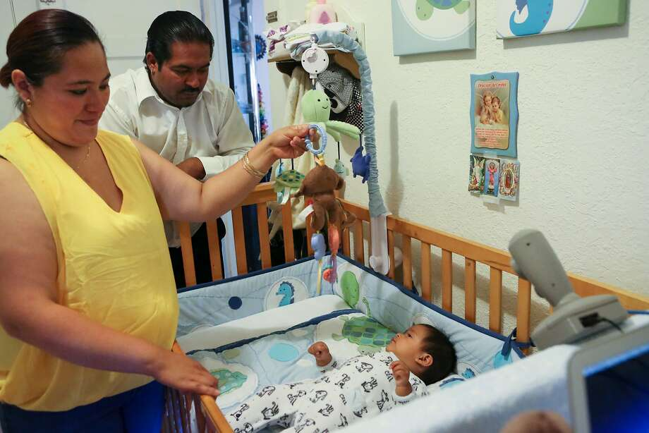 A Cocoon Cam prototype is demonstrated on 8 month old, Aryan Sohal, while parents Karla and Barinder keep him entertained in their home in Richmond, Calif. on Monday, August 10, 2015. Cocoon Cam allows parents to monitor their baby's respiration, heart rate and temperature without having to touch anything to the baby and without microwaves. Photo: Amy Osborne, Special To Chronicle