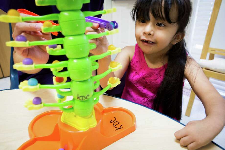 Ariel Reyes, 7, places marbles on a moving toy centipede as a way to practice her coordination skills at the Kids Development Center. Reyes, 7, was born with spina biffida and relies on physical therapy and occupational therapy to be able to develop the skills for the everyday tasks.   Wednesday, Aug. 5, 2015, in Houston . ( Marie D. De Jesus / Houston Chronicle ) Photo: Marie D. De Jesus, Staff / Houston Chronicle / © 2015 Houston Chronicle