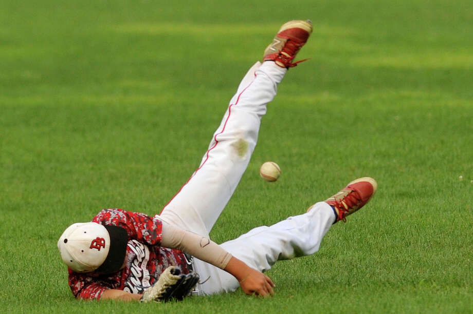 "The Hawks' Brett Locciasano dives unsuccessfully for a ball hit to short center field during their semifinal game against the Gators during the 29th annual Sharkey Laureno Memorial Baseball Tournament at Cubeta Stadium in Scalzi Park in Stamford, Conn., on Monday, Aug. 10, 2015. The Gators beat the Hawks 13-3 in six innings. Both teams are from Westchester County, NY. The tournament benefits the Sharkey Laureno Scholarship Fund, Inc., which provides college scholarships to graduates of Stamford's Junior Babe Ruth Baseball program that have finished their first year of post-secondary education. The Sharkey Laureno Tournament started in 1987 to honor the memory of longtime Stamford youth baseball coach John ""Sharkey"" Laureno whose passion was to help children on and off the field. Prior to the start of this year's tournament, over $300,000 has been awarded to over 140 graduates of the baseball program. Photo: Jason Rearick / Hearst Connecticut Media / Stamford Advocate"