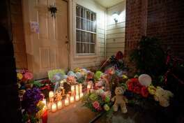 A memorial for the eight people killed is seen, Monday, Aug. 10, 2015, in Houston. Authorities said David Ray Conley had broken in through a window, armed and with handcuffs, and methodically shot his estranged ex-girlfriend Valerie Jackson, her husband and six children, including his own son, one by one in the head. All eight died in the house. (Cody Duty / Houston Chronicle)