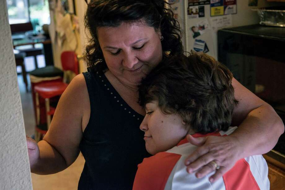 Cynthia Oyler, 17, who suffers from Spina Bifida, hugs her mother Nora Oyler in their family's home on August 10, 2015. Oyler benefited from the early childhood intervention program, which gave her access to physical therapy and other treatments after being born with the debilitating condition of Spina Bifida. Her therapy was at risk because of proposed cuts, but a judge on Wednesday decided to temporarily block tens of millions of dollars in planned Medicaid funding cuts, likely ensuring that thousands of children with disabilities will continue to access therapy services after Oct. 1. Photo: Matthew Busch /For The Express-News / © Matthew Busch