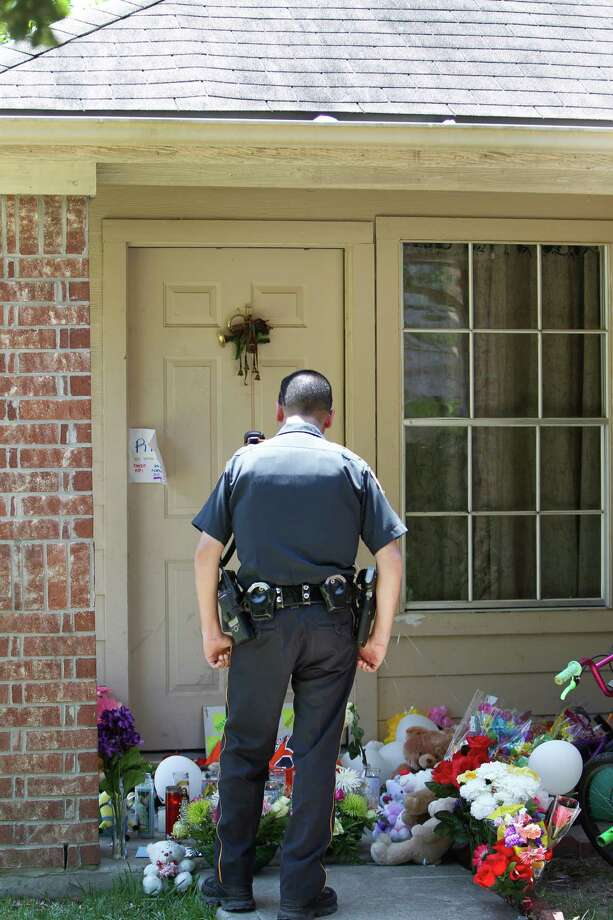 Harris County Sheriff's Officer E.A. Lopez pays his respects at the home where a couple and six children were slain Saturday night. Photo: Steve Gonzales /Houston Chronicle / © 2015 Houston Chronicle