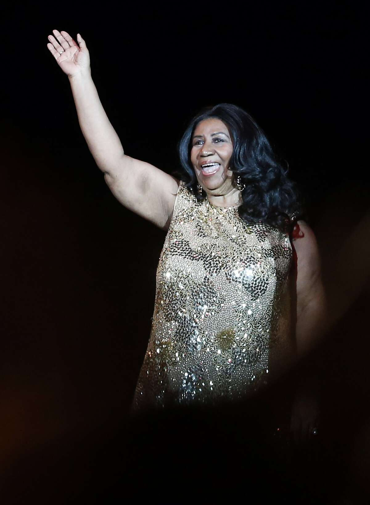 Aretha Franklin acknowledges the crowd as she takes to the stage to perform at Oracle Arena in Oakland, Calif., on Monday, Aug. 10, 2015.