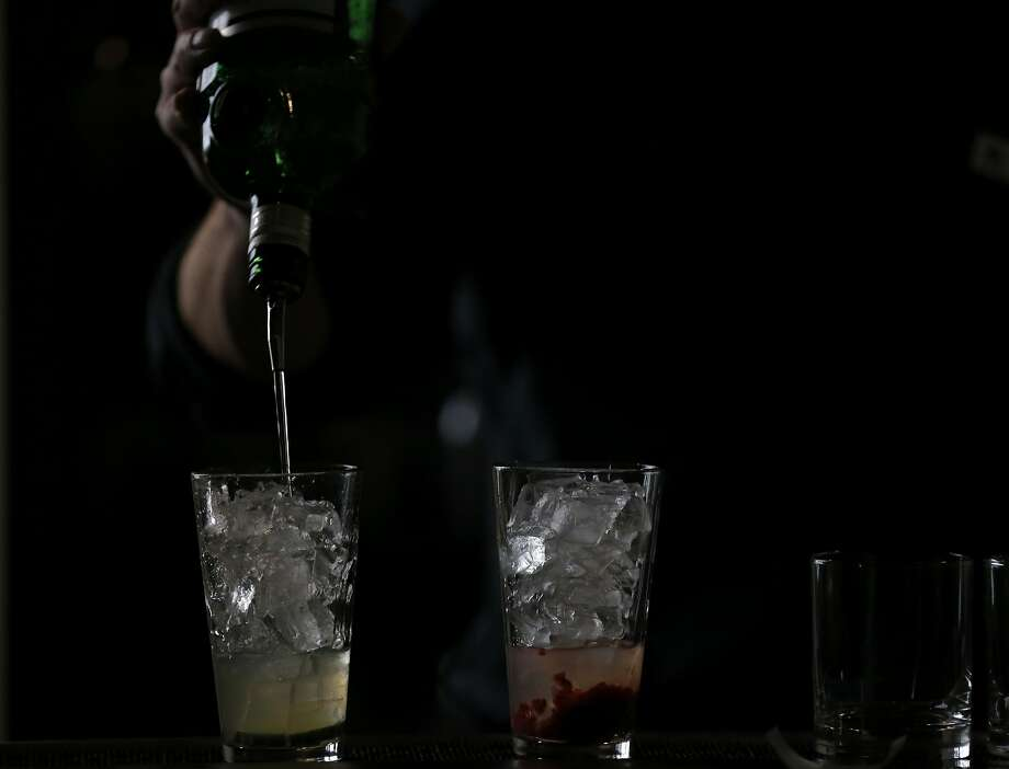 A bartender mixes two cocktails at the View in San Francisco. Photo: Connor Radnovich, The Chronicle
