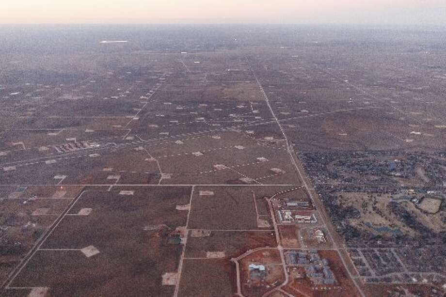 Oil well pads surrounding a development in Midland, Texas, Jan. 15, 2015. (Michael Stravato/The New York Times)