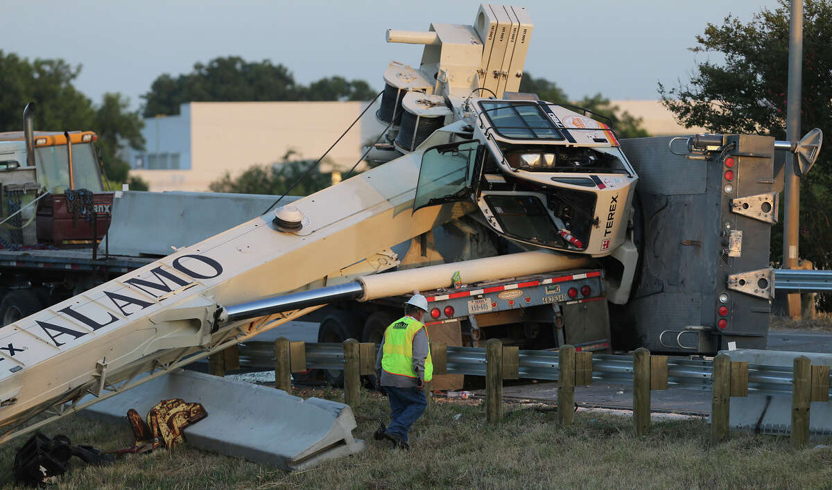 Crews work Tuesday August 11, 2015 to upright a crane that tipped over at the highway interchange of IH-10/US 90 westbound and IH-35 southbound. Traffic on the interchange has been blocked for hours while concrete barriers in the area are being moved. A private environmental response crew is also at the scene using an absorbent substance. It is currently unknown if there were any injuries at the accident.