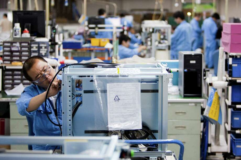 Employees at a General Electric facility in Beijing assembling medical devices in 2011. Photo: Nelson Ching / Bloomberg / 2011 Bloomberg Finance L.P.