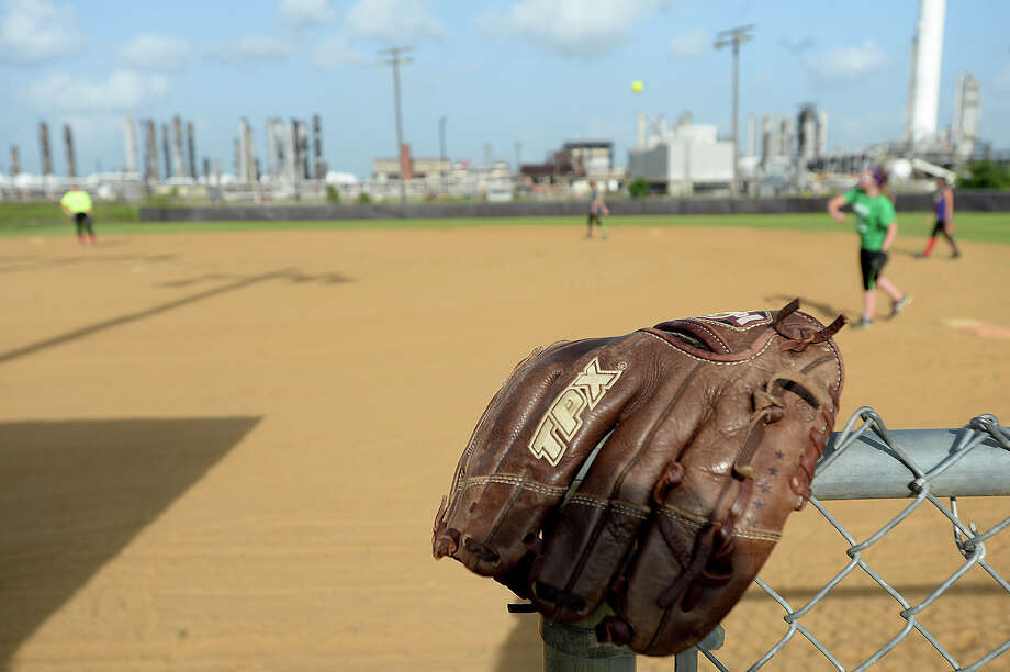 Members of the Port Neches - Groves Softball League state champions practice on their little league field Tuesday night. A development company looking to build on the open land off Merriman Road has raised concerns that the teams will lose their home fields, though the district's superintendent has said that there are no plans to tear down the fields. Photo taken Tuesday, July 07, 2015 Kim Brent/The Enterprise Photo: Kim Brent / Beaumont Enterprise