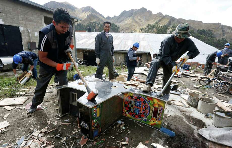 Workers use sledgehammers to smash a seized slot machine, in La Paz, Bolivia, Friday, Nov. 28, 2014. The Bolivian government has begun the nationwide destruction of thousands of slot machines and gambling tables confiscated from operators due to irregularities within the machines themselves and/or the illegal placement of the gambling equipment. Many were found to be operating near schools and attracting children to play. (AP Photo/Juan Karita) Photo: Juan Karita / Associated Press / AP