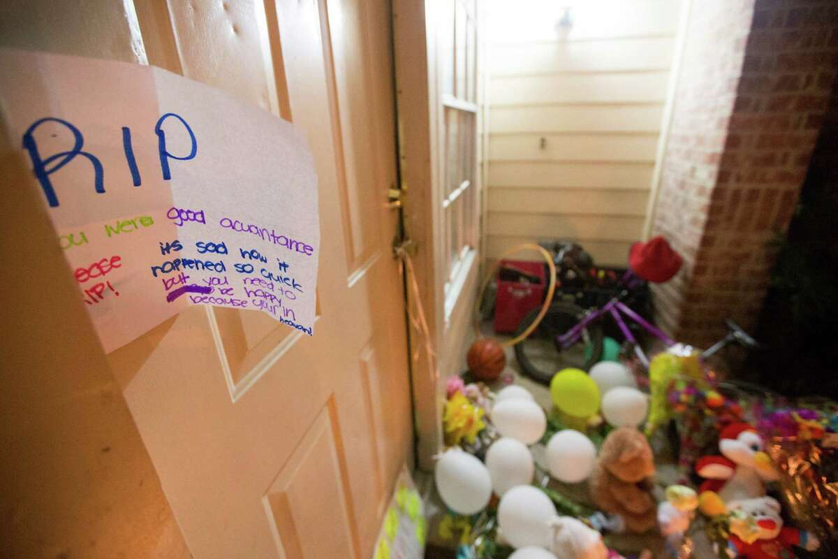 A memorial for the eight people killed is seen, Monday, Aug. 10. Authorities said David Ray Conley had broken in through a window, armed and with handcuffs, and methodically shot his estranged ex-girlfriend Valerie Jackson, her husband and six children, including his own son, one by one in the head. All eight died in the house.