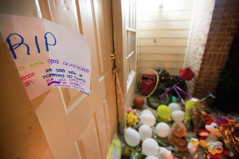 A memorial for the eight people killed is seen, Monday, Aug. 10. Authorities said David Ray Conley had broken in through a window, armed and with handcuffs, and methodically shot his estranged ex-girlfriend Valerie Jackson, her husband and six children, including his own son, one by one in the head. All eight died in the house. Photo: Cody Duty, Houston Chronicle / © 2015 Houston Chronicle