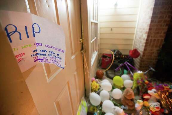 A memorial for the eight people killed is seen, Monday, Aug. 10, 2015, in Houston. Authorities said David Ray Conley had broken in through a window, armed and with handcuffs, and methodically shot his estranged ex-girlfriend Valerie Jackson, her husband and six children, including his own son, one by one in the head. All eight died in the house.
