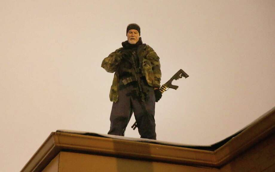 John Karriman. a volunteer from Oath Keepers, stands guard on the rooftop of a  business on November 26, 2014 in Ferguson, Missouri. Demonstrators looted and burned down several businesses along the street on Monday after the grand jury announced its decision in the Michael Brown case. Brown, an 18-year-old black man, was killed by Darren Wilson, a white Ferguson police officer, on August 9. Photo: Scott Olson, Getty Images / 2014 Getty Images