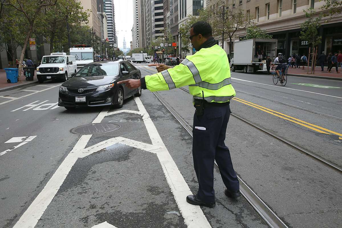 Badge #1 Michael Hayes directs traffic on Market at Third streets in San Francisco, Calif., on Tuesday, August 11, 2015. Enforcement of new turn restrictions on Market Street between Third and Eighth streets, designed to keep most private cars off of Market took effect on Tuesday.
