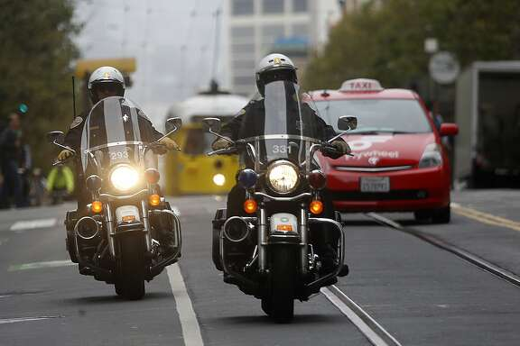 San Francisco police monitor traffic on Market at Third streets in San Francisco, Calif., on Tuesday, August 11, 2015.  Enforcement of new turn restrictions on Market Street between Third and Eighth streets, designed to keep most private cars off of Market take effect this morning.