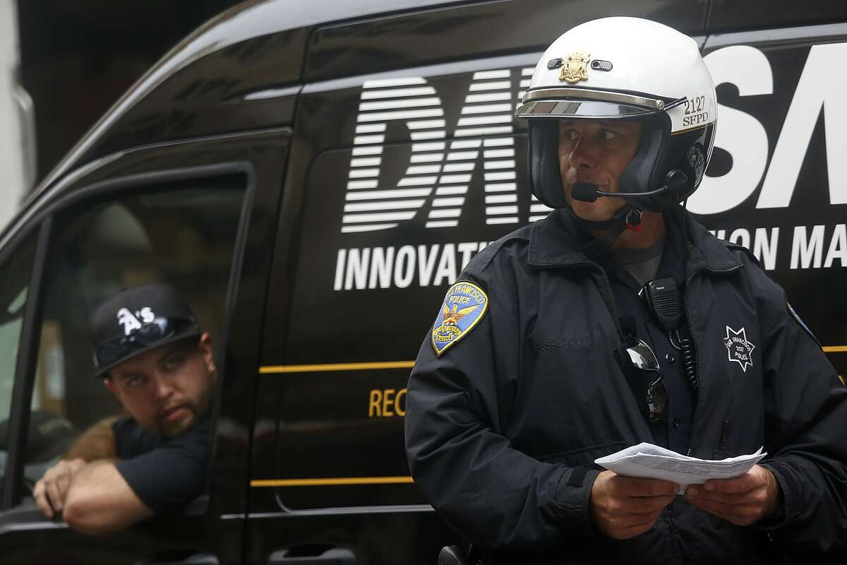 A police officer on Market at Third streets mentions he already issued four bikes running red lights on Market St. between Third and Eighth streets in San Francisco, Calif., on Tuesday, August 11, 2015.