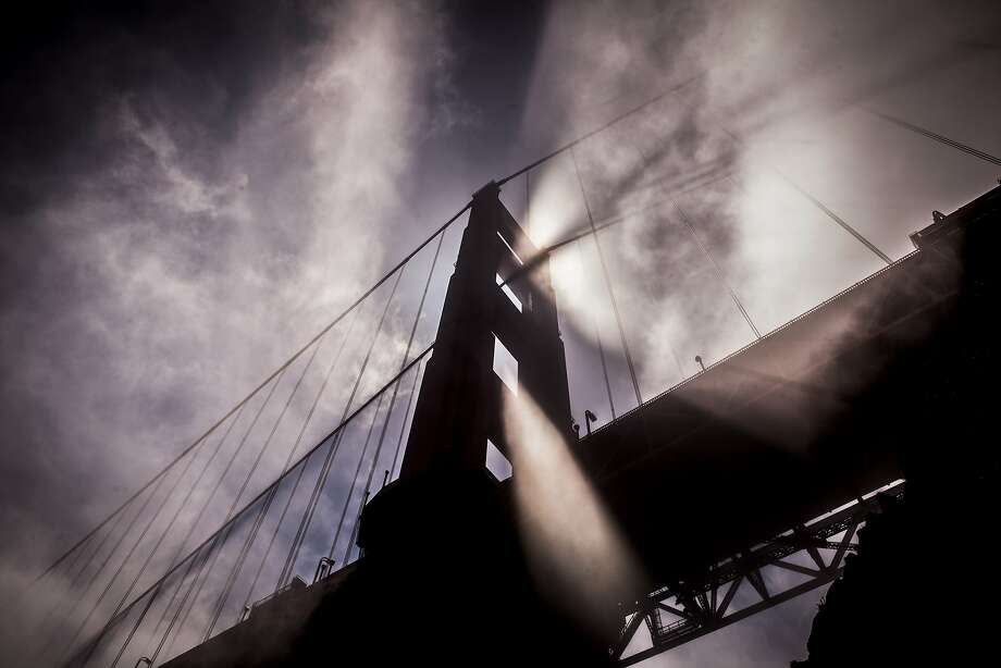 Afternoon light streams through fog blowing by the north tower of the Golden Gate Bridge. Photo: Russell Yip, The Chronicle