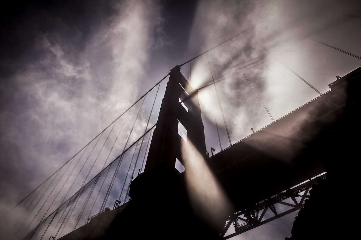 Afternoon light streams through fog blowing by the north tower of the Golden Gate Bridge on Tuesday, May 8, 2012.