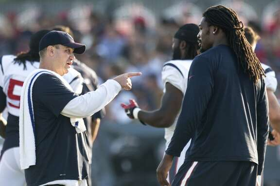 Houston Texans head coach Bill O'Brien talks to outside linebacker Jadeveon Clowney during Texans training camp at the Methodist Training Center Tuesday, Aug. 11, 2015, in Houston.  ( Brett Coomer / Houston Chronicle )