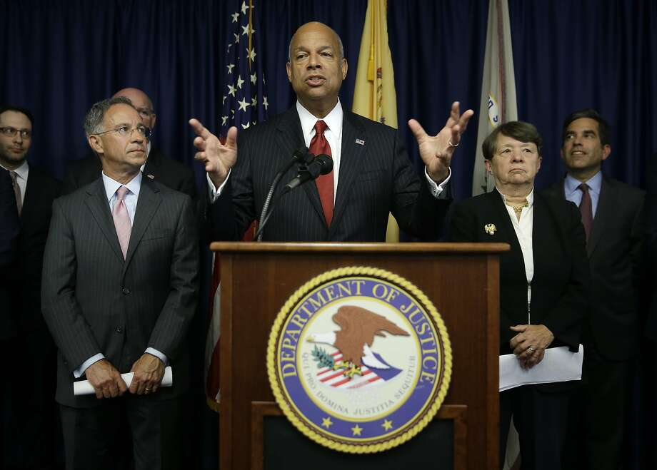 United States Secretary of Homeland Security Jeh Johnson, center, speaks during a news conference. During a visit to San Francisco, he criticized the city's policy of generally not cooperating with immigration officials. Photo: Seth Wenig, Associated Press