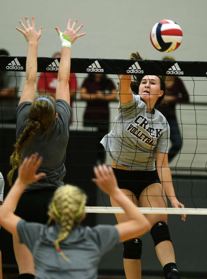 Clear Creek junior outside hitter Melissa McNeil, right, attacks the net against Barbers Hill during their scrimmage at Pearland earlier this month. Photo: Jerry Baker, Freelance