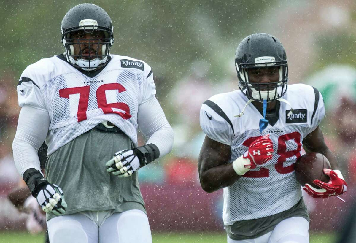 Houston Texans tackle Duane Brown (76) and running back Alfred Blue (28) run upfield during Texans training camp with the Washington Redskins at the Bon Secours Training Center on Saturday, Aug. 8, 2015, in Richmond, Va.