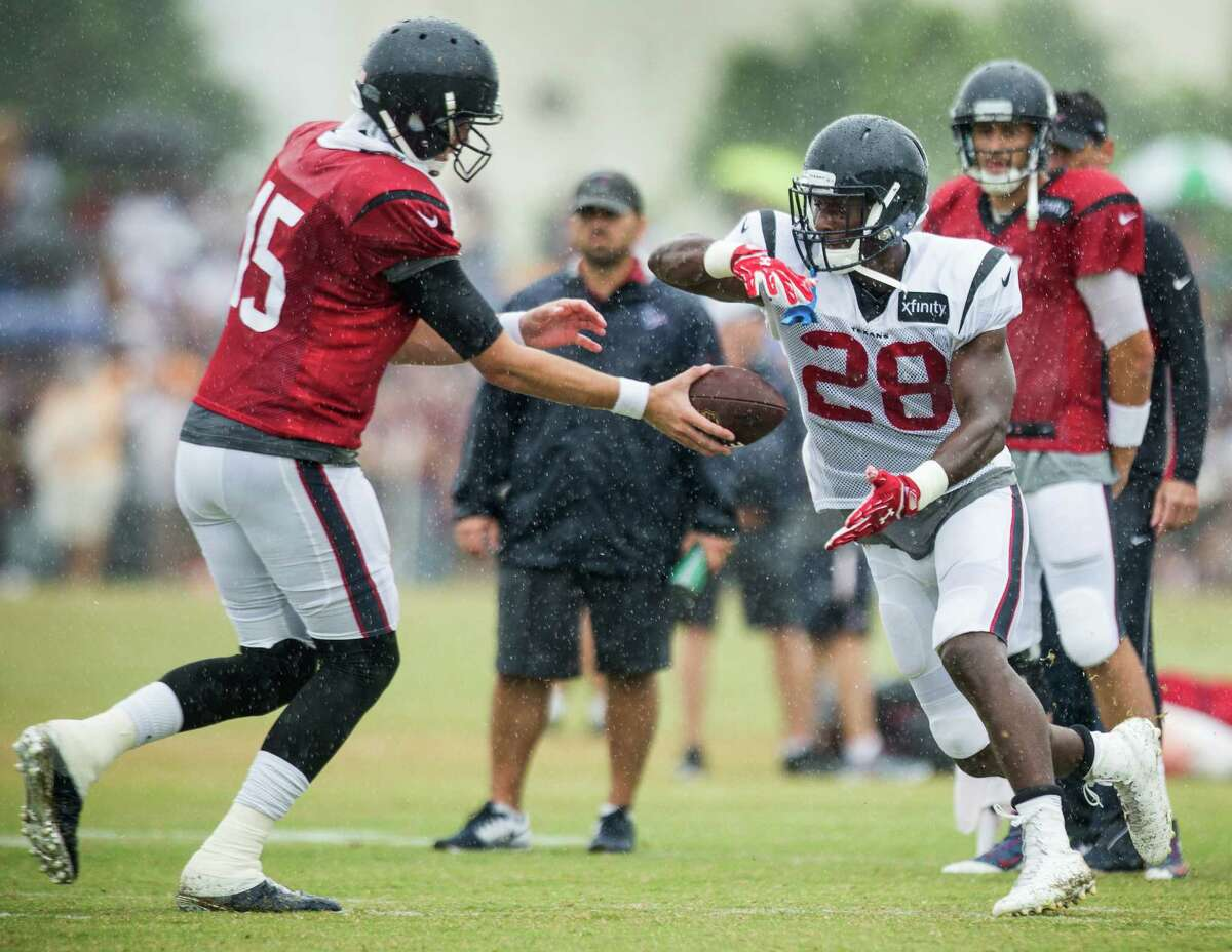 Houston Texans quarterback Ryan Mallett (15) hands off to running back Alfred Blue (28) during Texans training camp with the Washington Redskins at the Bon Secours Training Center on Saturday, Aug. 8, 2015, in Richmond, Va.