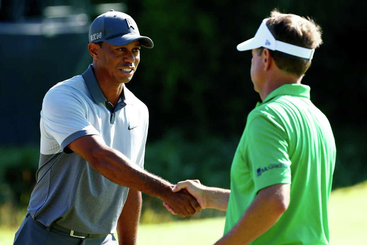 Tiger Woods and Davis Love III of the United States shake hands after playing together during a practice round prior to the 2015 PGA Championship at Whistling Straits on August 11, 2015 in Sheboygan, Wisconsin.