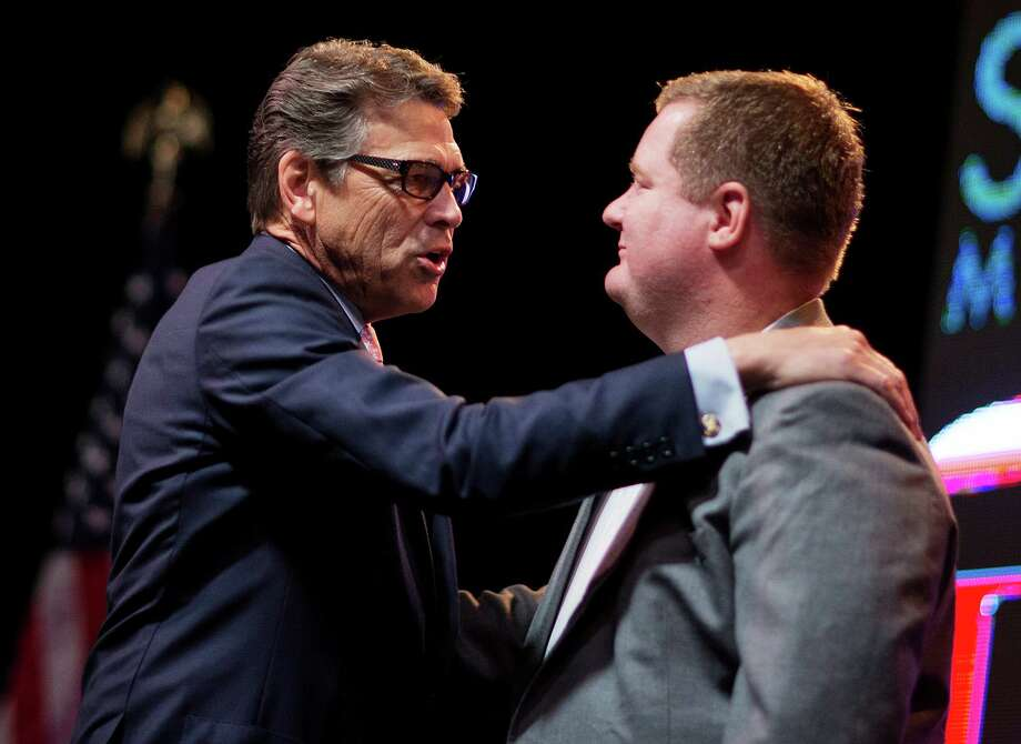 Republican presidential candidate Gov. Rick Perry embraces conservative blogger Erick Erickson at the RedState Gathering in Atlanta. The front page placement of a story on the financial woes of the Perry campaign, according to a reader, smack of an anti-Perry bias. Photo: David Goldman /Associated Press / AP